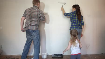 apaság : A happy family paints the wall with white paint, brunette mother and bearded father using rollers, little daughter apply paintbrush.