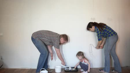 отцовство : A happy family paints the wall with white paint, brunette mother and bearded father using rollers, little daughter apply paintbrush.