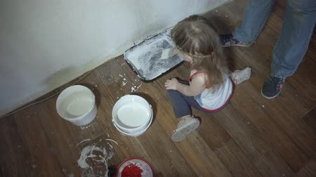 apaság : Daughter sitting on the floor next to the tray and buckets of paint, helps his parents done repair in the room, using paintbrush, next to the little girl visible female feet in jeans and sneakers.