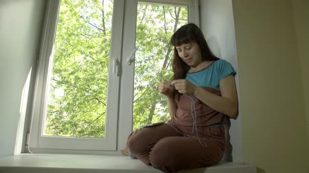 chunky : Young beautiful happy woman knits from blue yarn with knitting needles and uses smartphone sitting on window sill at bright spring day outside window trees with green leaves.