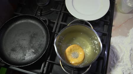 оладья : The process of cooking donuts. Doughnut fry in boiling oil in a small saucepan on a gas stove shooting from above.