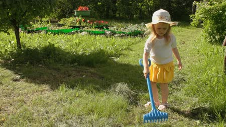 hay pile : A little sweet girl in a yellow skirt with a white blouse and a beautiful hat scoops the mown grass with blue rakes, helping the adults to work in the garden on a summer day.