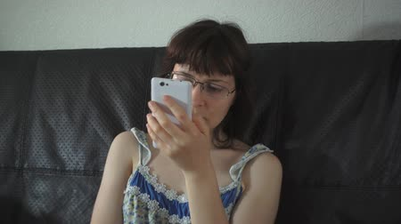 szieszta : A young woman with glasses and a colorful nightdress sits on a leather black couch and uses a white smartphone Stock mozgókép