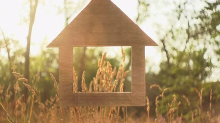 makler : A model of a miniature wooden house with a large window through which the ears of dry grass are seen, green trees and a pale sky in the rays of the setting summer sun.