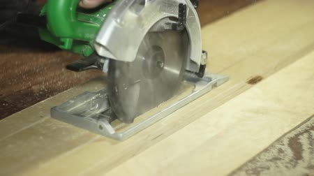 velo : A close-up shot of a manual circular saw sawing a sheet of plywood in a workshop. Male hands direct the blade along the marked line, the sawdust flies in different directions, slow motion.