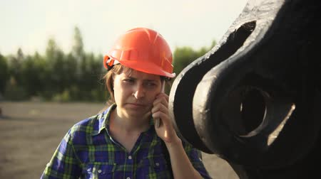 bailer : Portrait of a young woman worker in an orange helmet standing next to a large scoop mine excavator and communicating by phone.