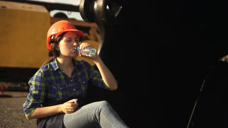 bailer : A young woman worker in an orange helmet sits in a large bucket of a mine excavator and drinks water from a plastic bottle Stock Footage
