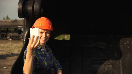 bailer : A young woman worker in an orange helmet sits in a large bucket of a mine excavator and take a selfie using a white smartphone camera.
