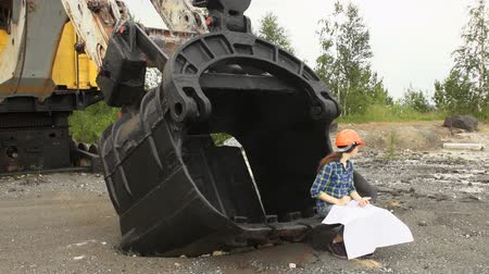 bailer : A female worker in a helmet examines a scheme sitting in a large bucket of a mine excavator. A young woman looks in different directions then checks the drawing with the help of a smartphone.