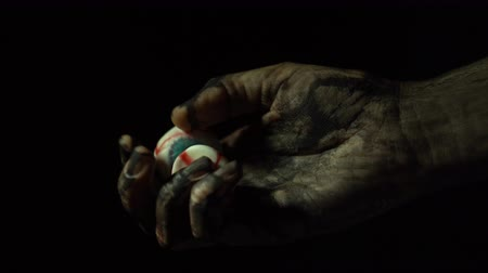 travessura : A close-up dirty zombie hand holds and rotates two eyes on a black background in a dark room.