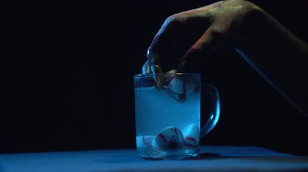 travessura : A zombies hand pulls out his eyes from a glass beaker with liquid shot against a black background close-up