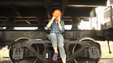 preocupações : An alarmed woman, a railway worker, sits on the frame of the chassis of the freight wagon, shakes her foot, wipes sweat from her forehead under the orange helmet, speaks on the phone. Stock Footage