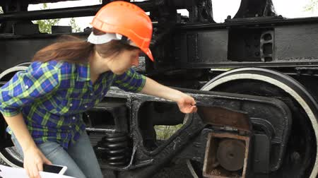 compares : A young brunette woman railway worker in an orange helmet checks the hitch unit of the freight wagon, raises the lid of the axle-box with a plain bearing and compares it with the circuit.