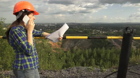 var : A young female worker in an orange helmet stand on a hill before fence over open pit , holds a document in her hand, then speaks on the phone. Stok Video