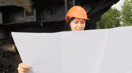 bailer : A young woman worker in orange helmet stands near a mining excavator and looks at the project then folds it and smiles. Stock Footage