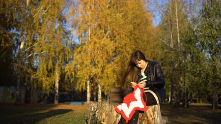 crochet : A young brunette woman in a black leather jacket crochets knit a red and white plaid in the shape of a star, sitting in an autumn or winter park. A girl makes a gift by hand for Christmas.
