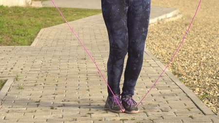 skákání : Female legs in dark blue leggings jump over the rope for the path next to the stony beach. Workout, outdoor activities in open air, slow motion.