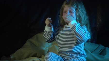 wipe away : A upset little girl in striped pajamas sits on the bed at night in her room and cries covering her face with her hands, then wipes away her tears and tries to calm down.