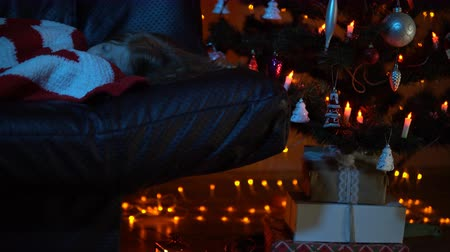bola de fogo : A nice little girl is sleeping on the couch under a striped red white plaid in the room, gift boxes stand under the Christmas tree at night. Stock Footage