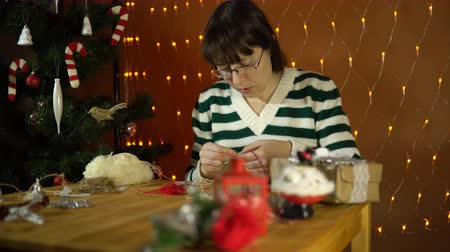 meada : A young brunette woman in a striped sweater is making ornaments in the form of a Christmas candy cane in the room on a background of yellow electric lights.