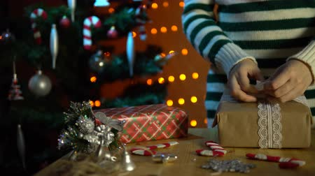 new clothes : A young woman in a striped sweater tie an openwork white bow on a box with a gift next to a Christmas tree in a room decorated with yellow electric lights.