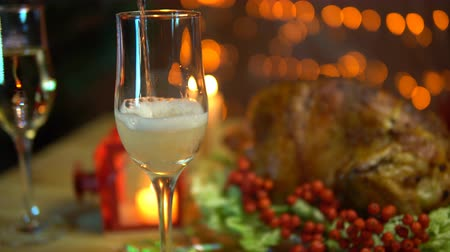 körítés : In the glass pour champagne next to the fried bird on a plate with a salad on the table on a background of yellow electric lights with a festive Christmas dinner in the evenings. Stock mozgókép