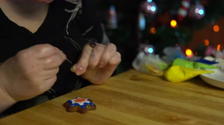 körítés : A mature woman decorates with icing homemade ginger cookie sitting at a wooden table next to a decorated Christmas tree in the evening on the eve of the holiday. Stock mozgókép