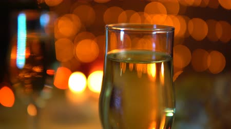 garnished : Glasses with champagne on a background of yellow electric lights with a festive dinner in the evenings Stock Footage