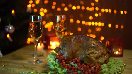 благодарение : A roasted bird on a platter with a salad next to a glass of champagne stands on a table amidst yellow electric lights with a festive dinner in the evenings. Стоковые видеозаписи