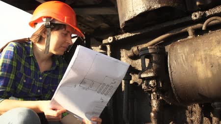 lom : A young woman engineer in an orange helmet checks the condition of the hydraulic system of a career excavator, using the scheme.