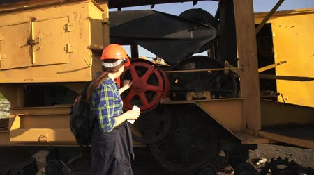 lom : A young woman worker in orange helmet stands near a yellow old excavator and use a white telephone.