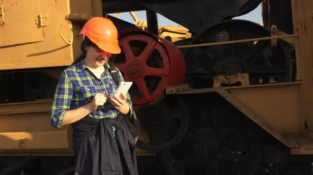 bailer : A young woman worker in orange helmet stands near a yellow old excavator and use a white telephone.