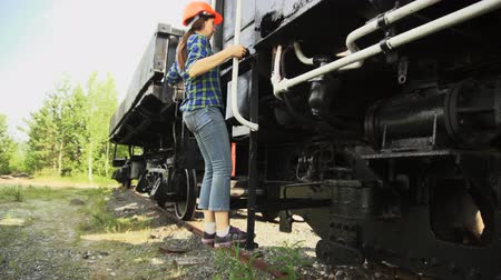 siding : A young woman railway worker in an orange helmet get down the stairs from the cargo wagon then walking beside the train past the camera Stock Footage