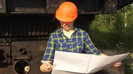 bailer : A young woman worker in orange helmet stands near a mining excavator, looks in the project then talking on the phone.