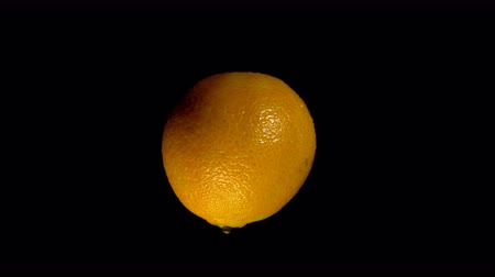 tangerina : Close-up rotation tangerine covered by drops of water. Fresh orange citrus isolated on black background.