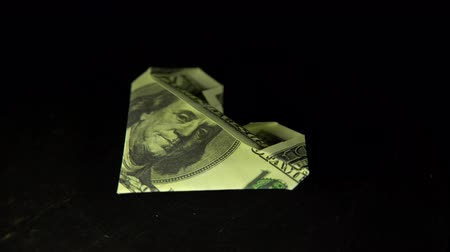 dobrado : The heart, folded from a dollar bill, revolves against a black background, the concept of accumulation for important events.