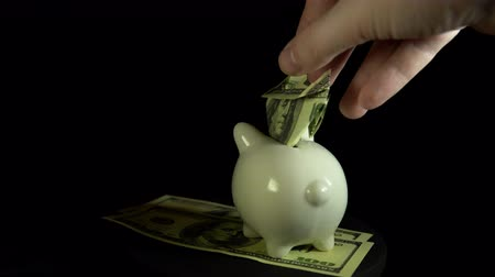 piggy bank : A white piggy bank and dollar bills revolve against a black background, saving and accumulating money.