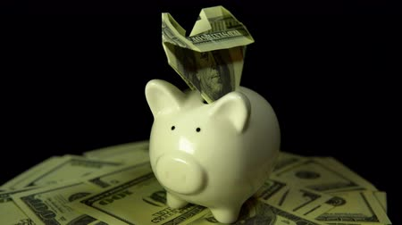 dobrado : A white piggy bank and dollar bills revolve against a black background. Heart of money stuck in a coin box.