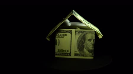 benefício : A white piggy bank and a model of a house from dollar bills revolve against a black background, the concept of saving and accumulating money. Stock Footage