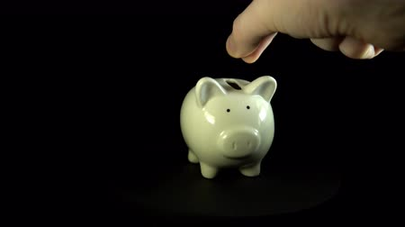 unknown : A white piggy bank revolve against a black background, an unknown person puts a heart in a money box , close-up.