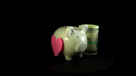 accumulating : A white piggy bank with a heart on its side and dollar bills revolve against a black background, saving, accumulating money for important moments of life