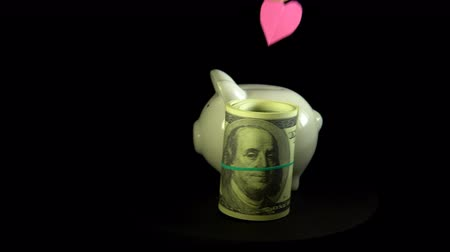 piggy bank : Close-up an unknown person puts a heart in a white piggy bank, which is rotating together with dollar bills against a black background, saving and accumulating money for important moments of life.