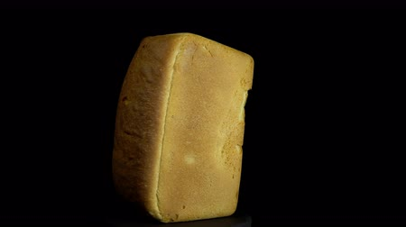 rotational : Close-up of fresh white wheat bread with golden crust revolves on a black background, looping.