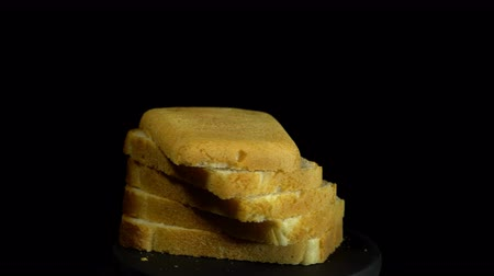 rotační : Close-up of sliced white wheat bread rotates against a black background, loopy motion.