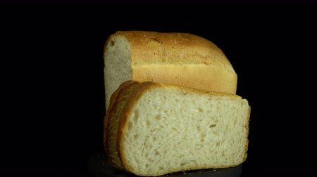 cereal product : Close-up of fresh white wheat bread with golden crust revolves on a black background, looping.