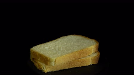 хлеб : Close-up of sliced white wheat bread rotates against a black background, loopy motion.