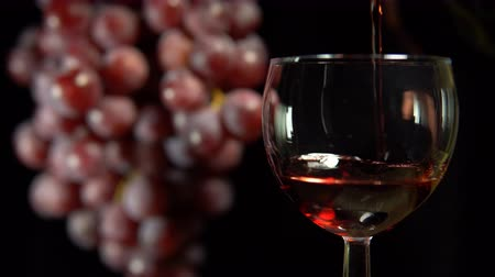 повод : Red wine is poured into a glass next to rotating the grapes. A pink alcoholic drink pours from a bottle on a black background. Стоковые видеозаписи