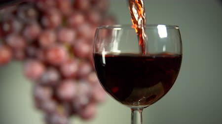 someone : Red wine is poured into a glass next to rotating the grapes. A pink alcoholic drink pours from a bottle on a light background. Stock Footage
