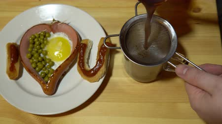 uznání : Someone pours coffee in a glass mug. Edible confession of love from toast and fried eggs is on a plate. A festive breakfast on a light wooden table. Dostupné videozáznamy