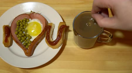 prohlášení : Edible confession of love from toast and fried eggs is on a plate. Someone stirs coffee or cocoa in a glass mug. Dostupné videozáznamy